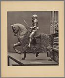 Arrangement of a sculpture of a horse with a textile saddle and a harness