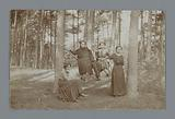 Group portrait of a four unknown women and a man around a hammock in a forest