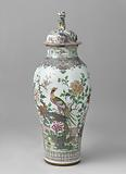 Baluster covered jar with pheasants on a rock near a fence and flowering plants