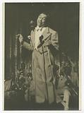 Print of Cab Calloway in checked suit standing in front of microphone