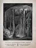 Geology: visitors climbing the large stalactites in a cave at Montserrat