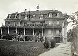 Vienna (?), Austria: a large house with people grouped on the verandah