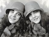 Daisy and Violet Hilton, conjoined twins, head and shoulders, wearing fur coats