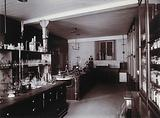 The interior of a pharmaceutical or chemical laboratory, with two long benches in the centre and glass-fronted …