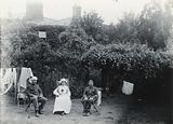 A nurse and two soldiers, one of whom has a bandage on his head, sitting on deck chairs in a garden with blossom trees …