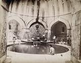 Bursa, Turkey: bath of Suleiman the Magnificent, with men sitting around the sides of a circular pool in a domed …