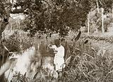 Mwera, Zanzibar, Tanzania: an African man stands in a river using a ladle to dip for mosquito larvae
