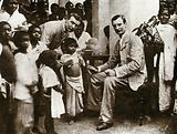 Inoculation against cholera: two men in suits prepare to inoculate a child, surrounded by a crowd of parents and …
