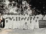 Leper settlement, Fianarantsoa, Madagascar: a group portrait of patients in white robes, with an elderly woman …
