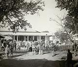 A hospital building, India (?), with men in turbans grouped outside