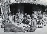 Africa: a medicine man sits with a circle of people including a sick child under a blanket
