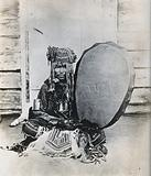 Siberia: a Tungus medicine man in ceremonial dress, seated holding a drum