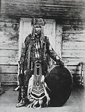 Siberia: a Tungus medicine man in ceremonial dress, standing holding a drum
