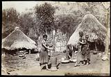 South Africa: Magwamba women grinding corn outside mud huts