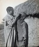 South Africa: a Pondo tribesman attends to the hairstyle of a fellow tribesman