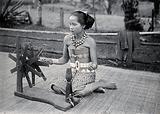 Sarawak: a native girl spinning cotton into thread