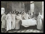 Medical staff standing round a woman patient in bed in a hospital ward