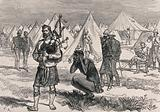 A man is playing the bagpipes on a camp site, as others walk around apparently oblivious to the sound, one man is …
