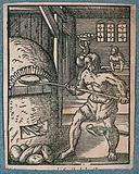 A baker is loading uncooked dough into the ovens, as bread is being carried in baskets on a man's head