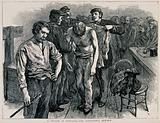 A man's shirt is being laid over his shoulders by a man in uniform, another holds his arm and a man stands nearby with …