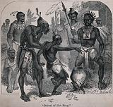Methods of torture in Africa: a man is forced to catch a very hot iron ring with his bare hands above a cauldron over …
