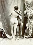 Two women posing naked in a photographic studio, standing embracing each other in front of some studio props
